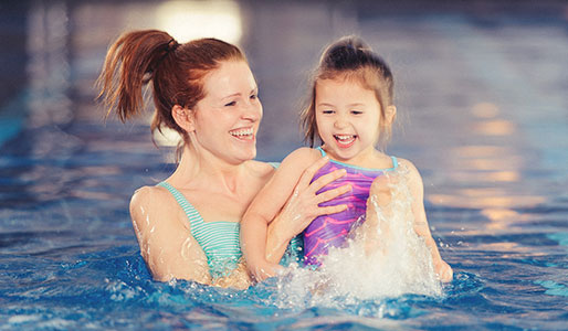 Lady in pool at Harbour Club Chelsea, with young daughter, smiling.