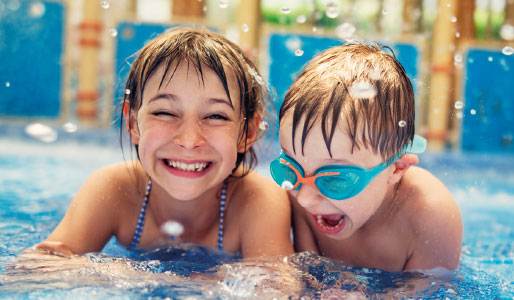 2 children playing in a swimming pool as part of DL Kids Summer Holiday Club.