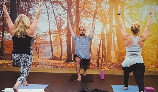 Image of a man leading a Yoga class with two women.
