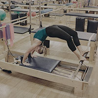 A woman using a Reformer Pilates bench at Harbour Club