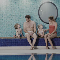 Image of family sat next to swimming pool