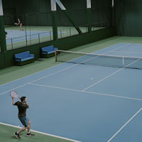 Image of man hitting a forehand on tennis court