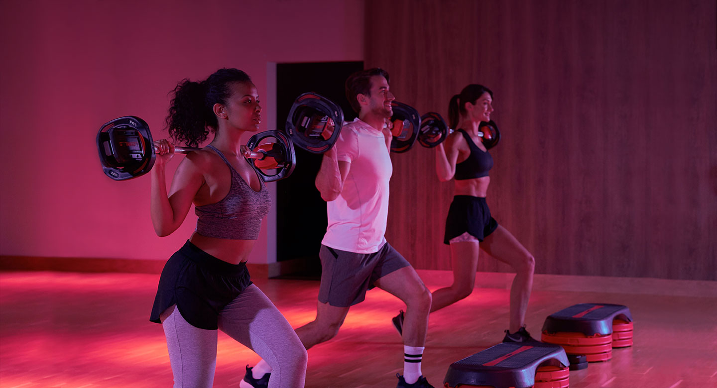 A group of people doing lunges, while holding barbells on their backs, during a Bodypump class at Harbour Club