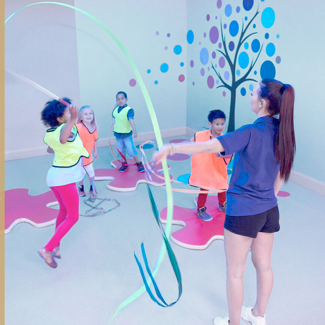 A group of children playing with gymnastic ribbons at Harbour Kids Club