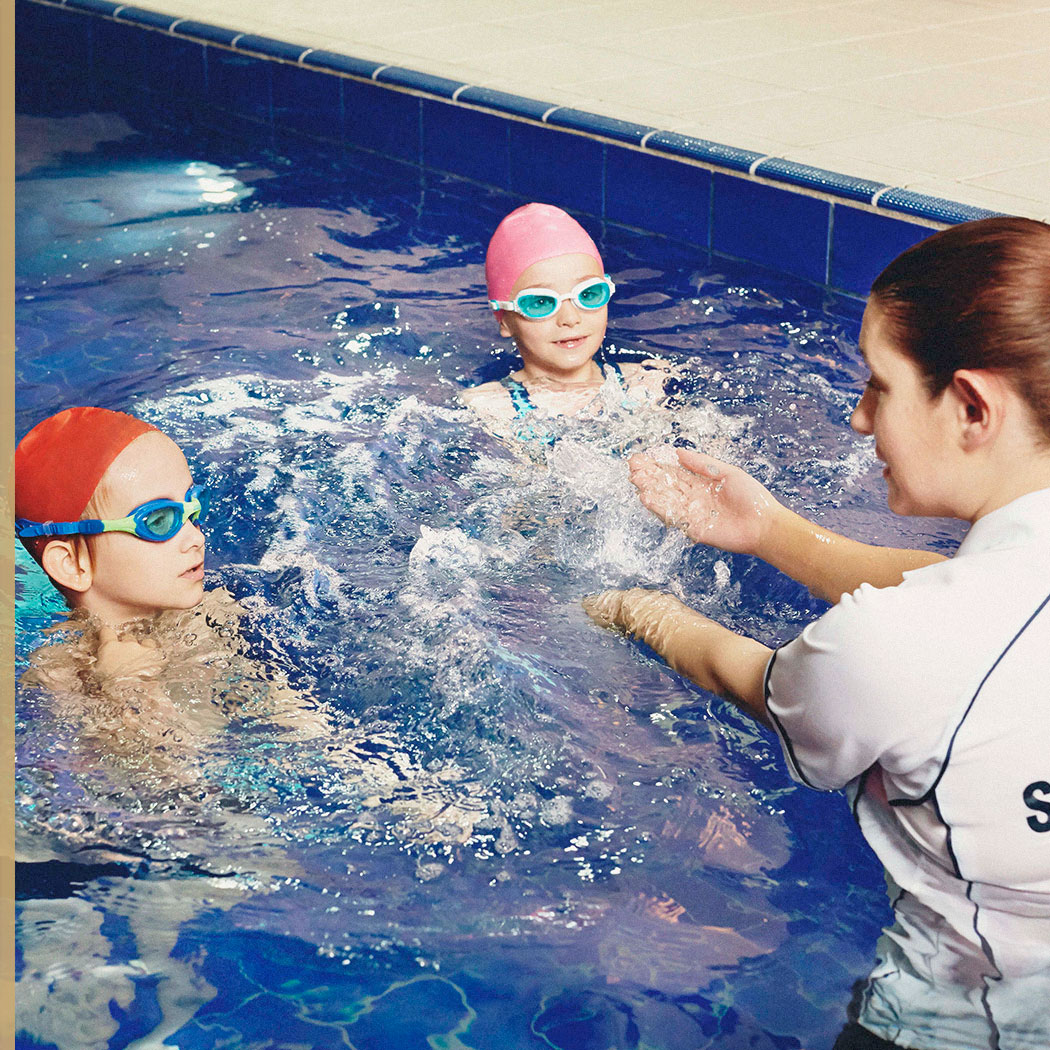 2 children receiving swimming instructions from a coach at Harbour Club
