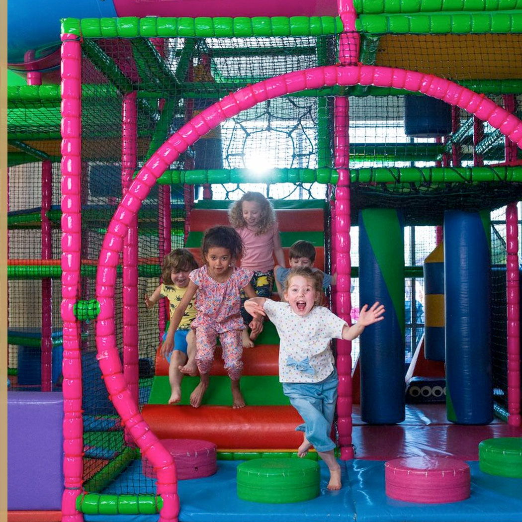 Children running around and laughing in soft play area at Harbour Club