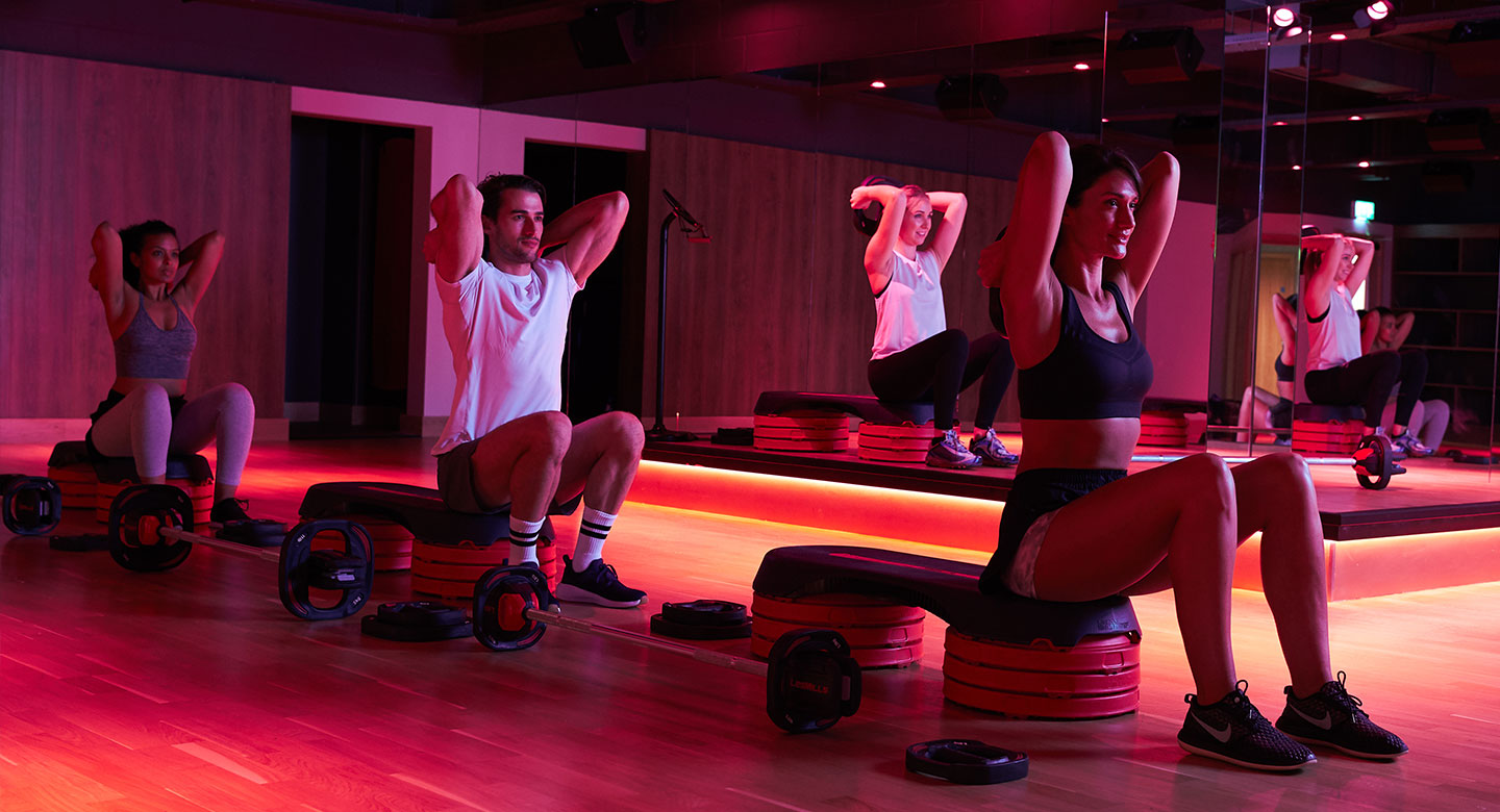 A group of people working their triceps during a Bodypump class at Habour Club