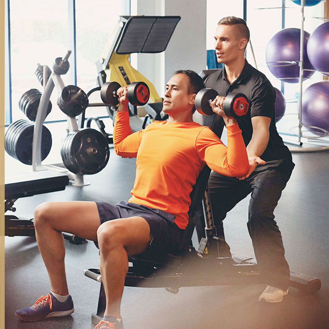 A man doing a chest press with dumbbells, being supported by a Personal Trainer, at Harbour Club