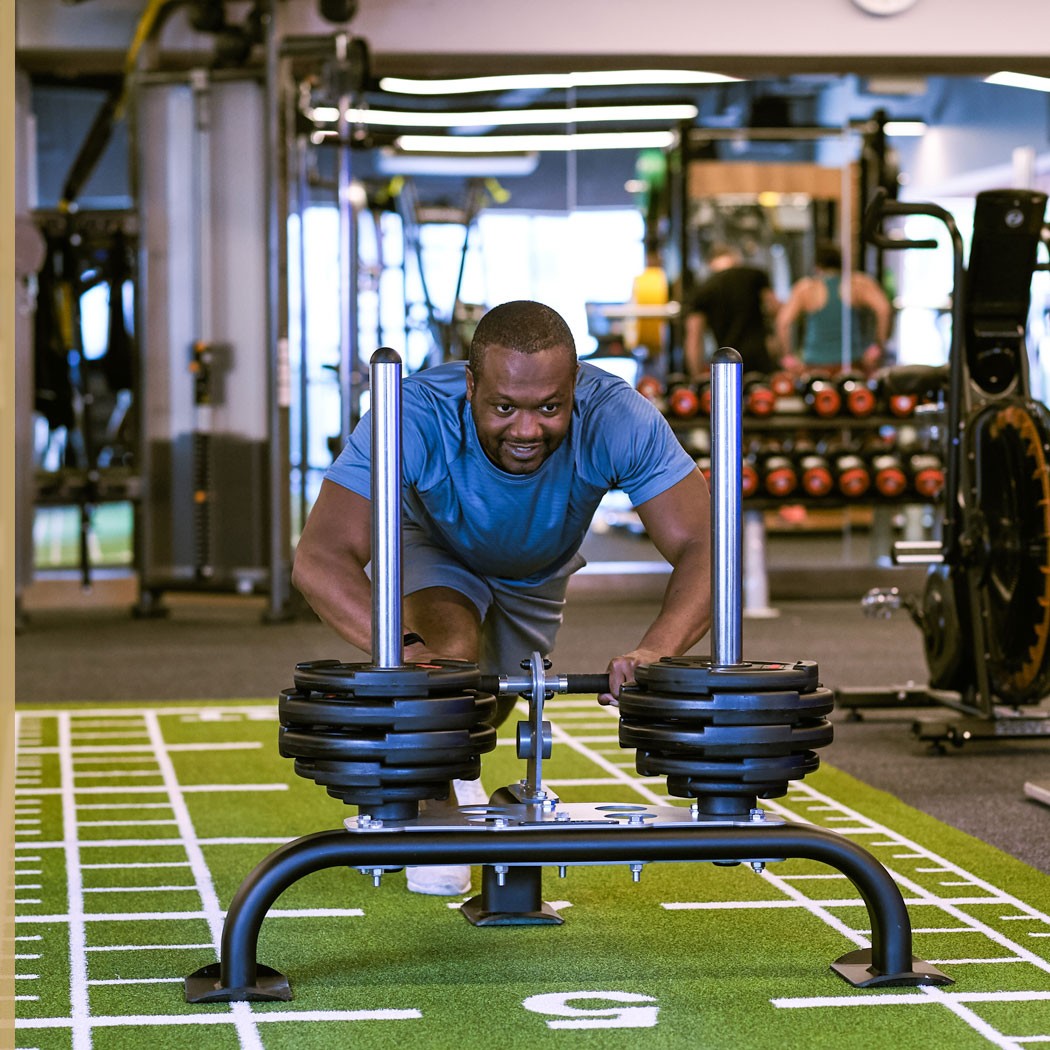 Image of man pushing sled in gym at Harbour Club