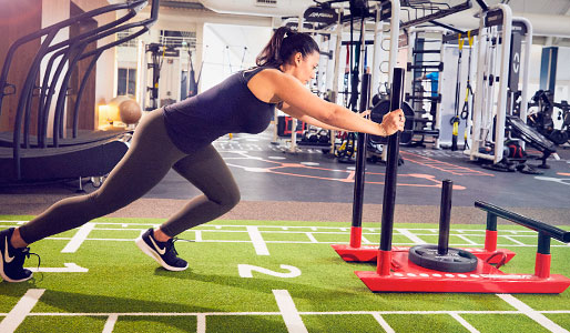 Image of a woman pushing a sled in the gym