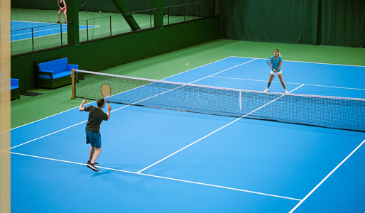 Image of man and woman playing tennis at Harbour Club Chelsea