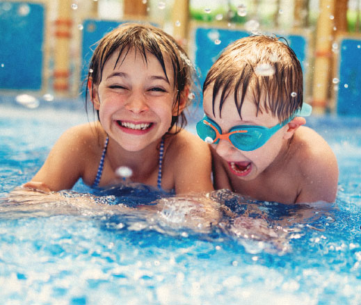 2 children playing in a swimming pool as part of the Summer Holiday Club.